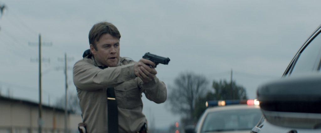 Luke Hemsworth als Cop steht in Tag der Vergeltung - Ein Vater sieht rot mit gezückter Waffe vor einem Auto.