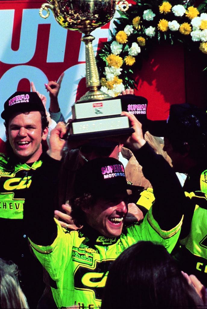 Tage des Donners-Hauptfigur Cole Trickle (Tom Cruise) hat gerade ein Rennen gewonnen. Er lächelt und hebt einen großen Pokal über seinen Kopf. Seine Boxencrew feiert mit ihm.