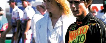 """In Tage des Donners spielen Nicole Kidman und Tom Cruise mit. Beide stehen an der Rennstrecke. Kidman trägt ein weißes Hemd und einen weißen Blazer darüber. Cruise steht zur ihrer linken Seite und hat einen schwarzen Renn-Overall an, mit orangener und grüner Aufschrift """"Mello Yello"""". Vor ihnen steht ein Rennauto dessen Dach man nur erkennen kann."""