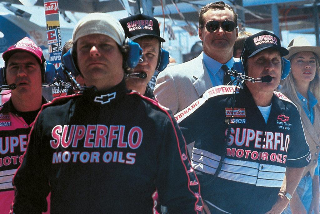 Die Boxencrew schaut gebannt auf die Rennstrecke. Robert Duvall hat dabei ein Headset auf. Hinter ihm steht Teamchef Randy Quaid, der einen beigen Anzug trägt.