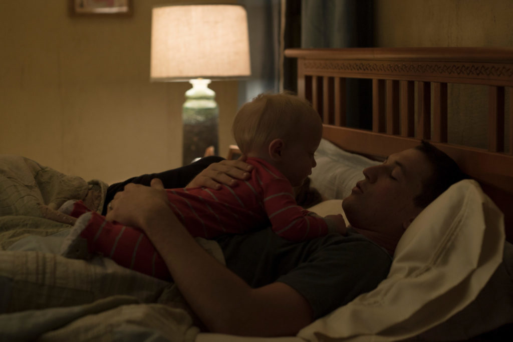 Mies teller als Schumann liegt im Bett und hat sein Baby auf seinem Bauch liegen.