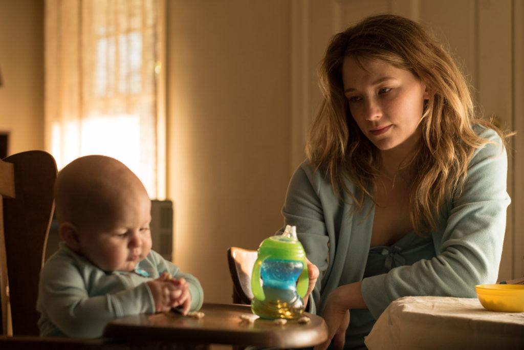 Haley Bennett als Amy Schumann sitzt in Thank You for Your Service mit ihrem Baby allein am Esstisch.