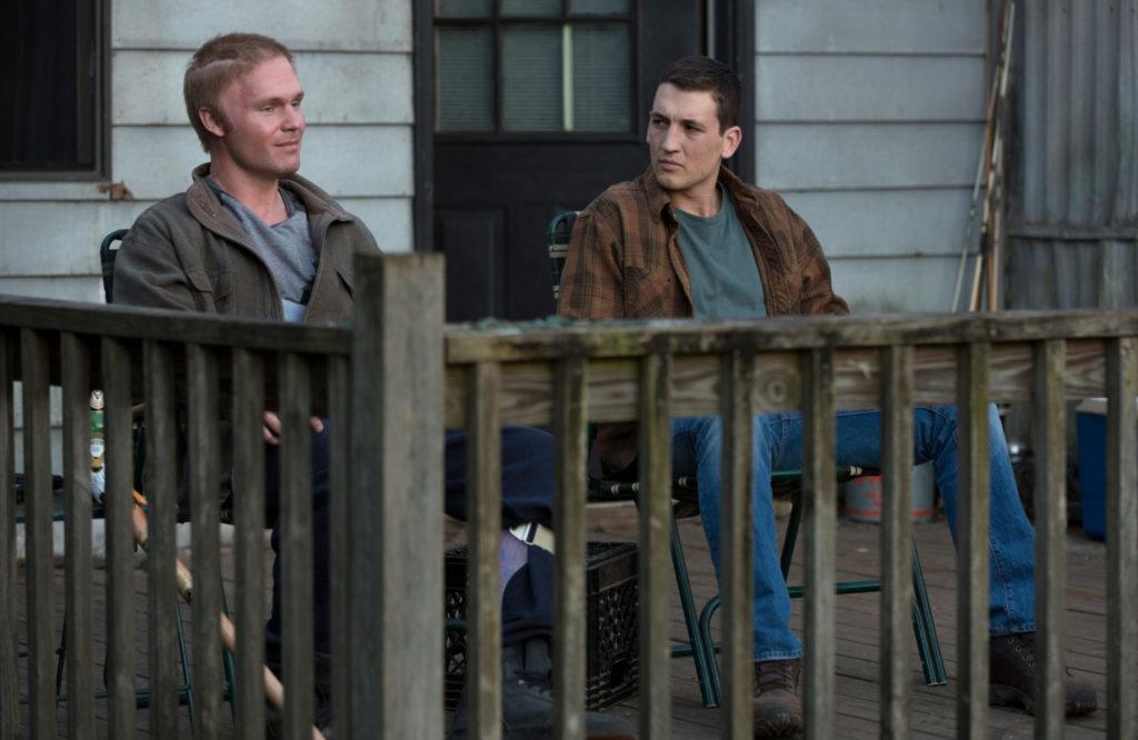 Miles Teller als Schumann sitzt mit Scott Haze als Emory auf der Veranda von Emorys Haus. Beide reden miteinander.