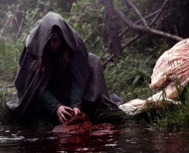 Rebecca Acock als Alice wäscht in The Cleansing - Die Säuberung im Fluss die blutigen Laken ihrer Mutter.