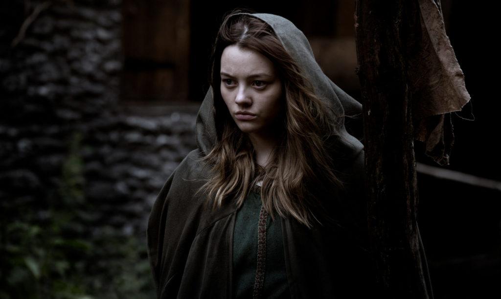 Alice, gespielt von Rebecca Acock, steht im Kapuzenumhang vor ihrer Hütte. Sie trauert um ihre ermordete Mutter.