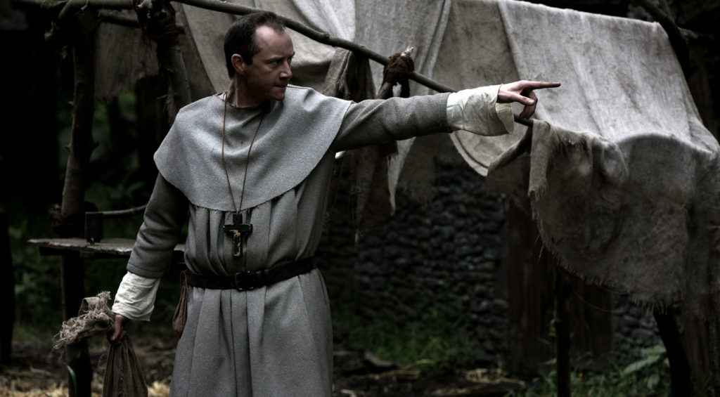 Dorfpfarrer Thomas, gespielt von Rhys Meredit, steht in The Cleansing - Die Säuberung auf dem Dorfplatz mit ausgestrecktem Arm. Er verbannt Alice aus der Gemeinschaft.