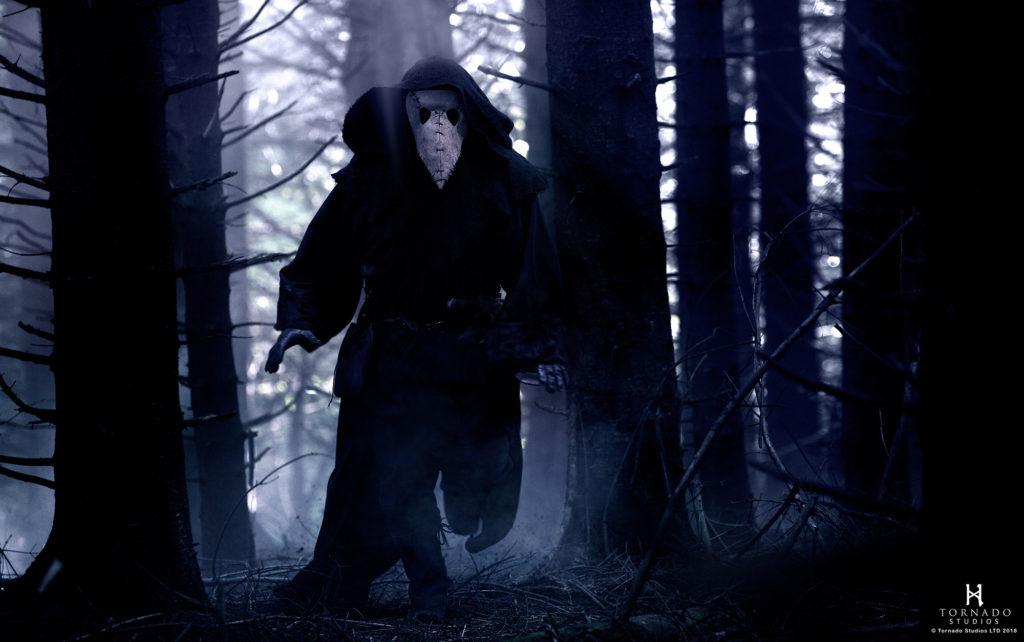 Der Läuterer rennt durch den Wald. Er trägt eine lange schwarze Kutte und unter seiner Kapuze eine vogelkopfartige Pestmaske.
