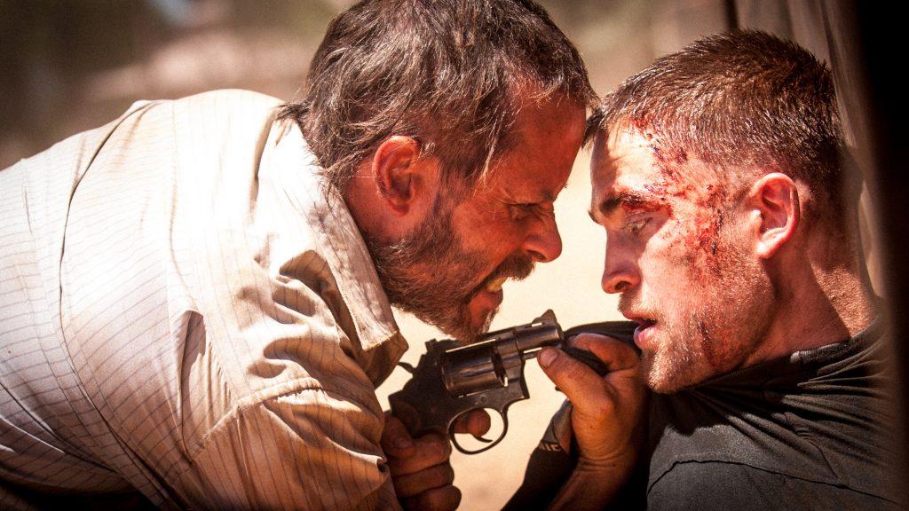 Guy Pearce bedroht den auf dem Boden sitzenden Robert Pattinson mit einem Revolver in The Rover.