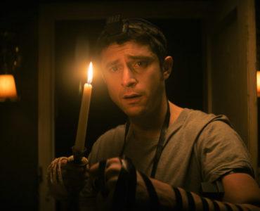 Yakov (Dave Davis) durchschreitet in THE VIGIL mit einer Kerze die Dunkelheit im mysteriösen Haus des Verstorbenen.
