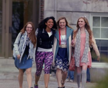Vier Mädchen verlassen lachend ein Schulgebäude in The Witch Files.