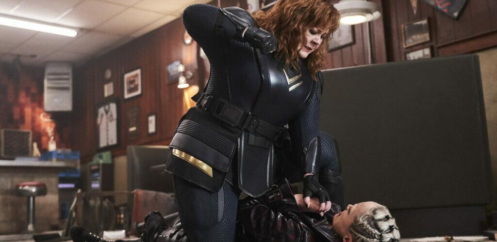 Melissa McCarthy sitzt auf einer Fraue und droht sie zu verprügeln