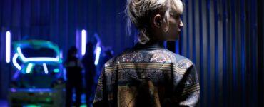 Alexia in Lederjacke, mit dem Rücken zur Kamera in Titane
