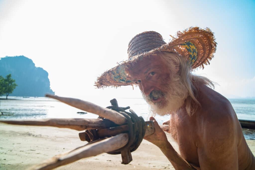 Burt Gummer (Michael Gross) verteidigt sich zurückgezogen auf einer einsamen Insel mit einem selbstgebauten Speer.