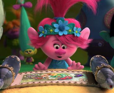 Poppy steht vor einem Tisch und studiert eine Karte, Branch steht im Hintergrund, Trolls World Tour