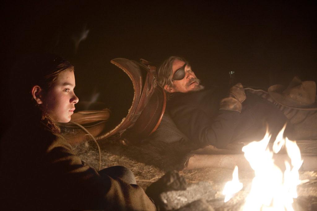 Mattie und Cogburn sitzen am Feuer, beide sehen bedrückt aus