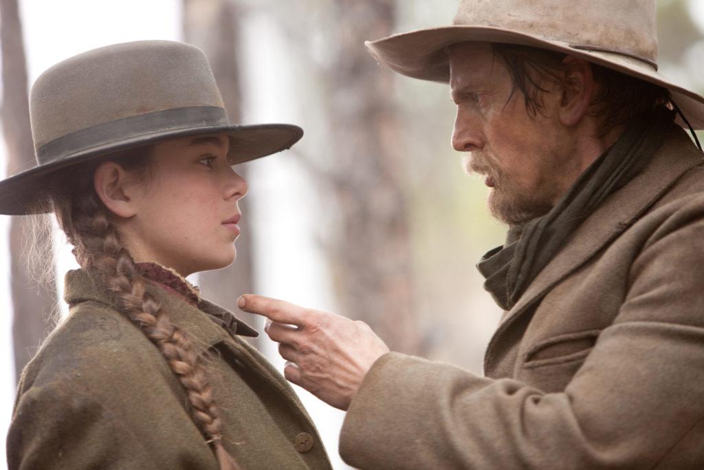 Mattie wird von einem Banditen zurechtgewiesen, er zeigt mit dem Finger auf sie, sie schreckt zurück