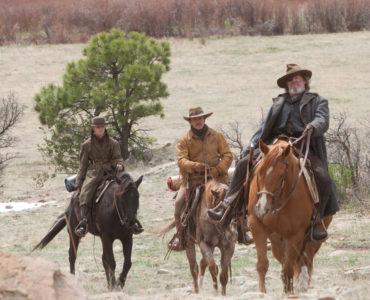 Cogburn, Mattie und LaBeauf reiten der Kamera entgegen durch eine Wüste