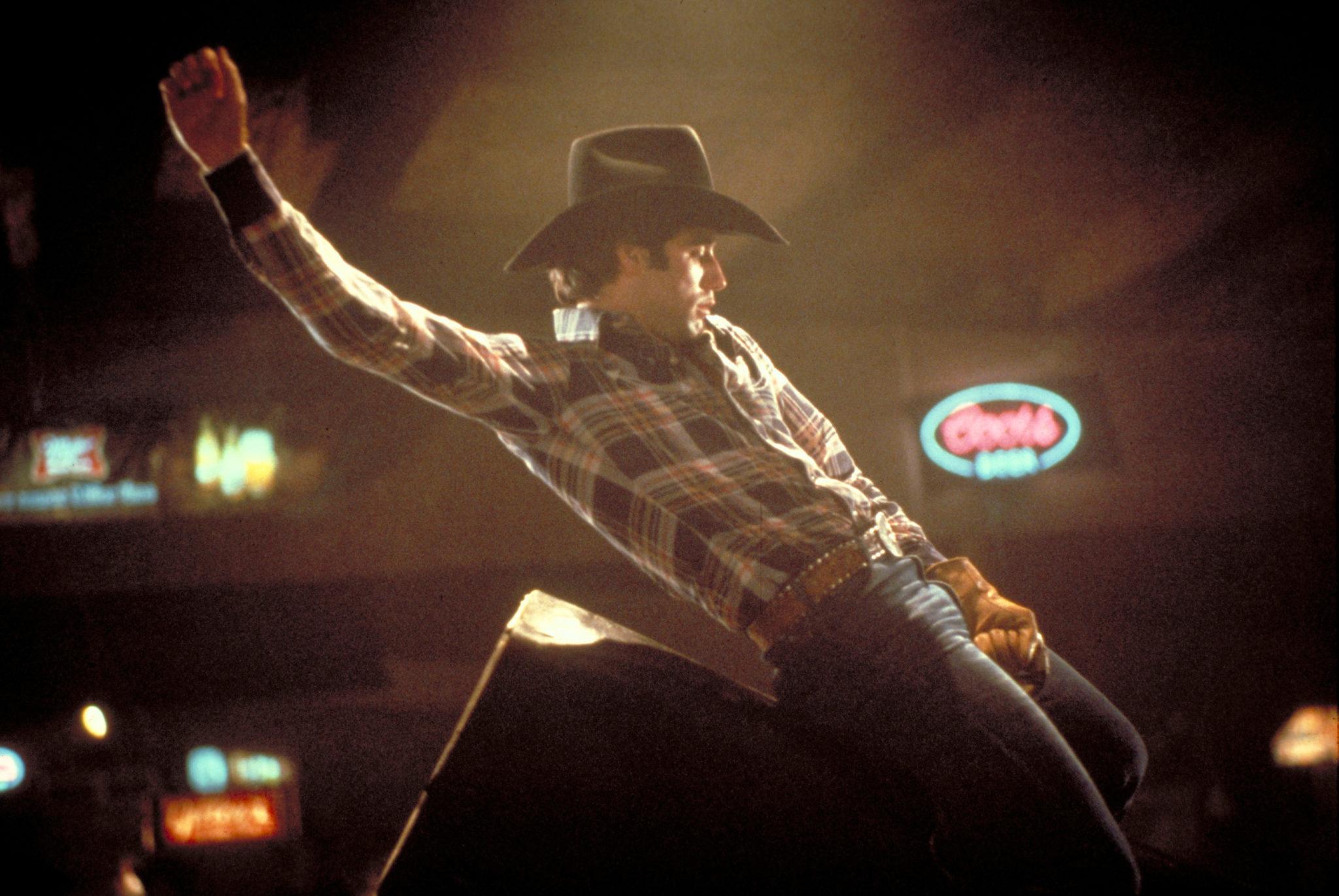 """John Travolta reitet als Bud Davis in """"Urban Cowboy"""" auf einem mechanischen Rodeobullen."""