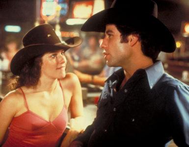 """Debra Winger als Sissy blickt John Travolta als Bud Davis in """"Urban Cowboy"""" leidenschaftlich an, während sich dieser an einem Bartresen mit ihr unterhält."""