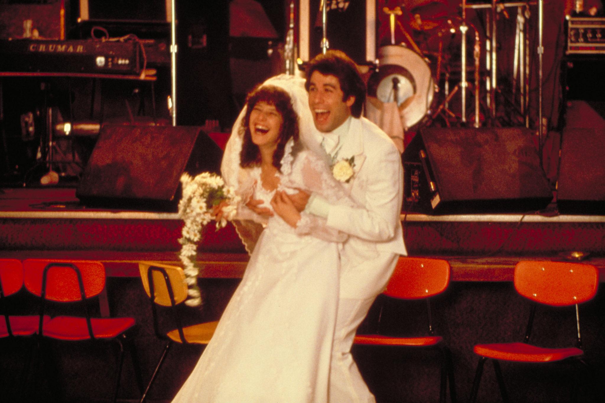 """John Travolta als Bud und Debra Winger als Sissy sind in """"Urban Cowboy"""" lachend als weiß gekleidetes Ehepaar zu sehen."""