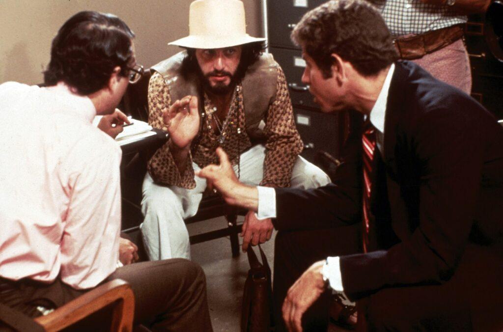Mit Vollbart und schrulligem Kostüm redet Serpico vorgebeugt mit einem Kollegen und einem Journalisten in dessen Büro