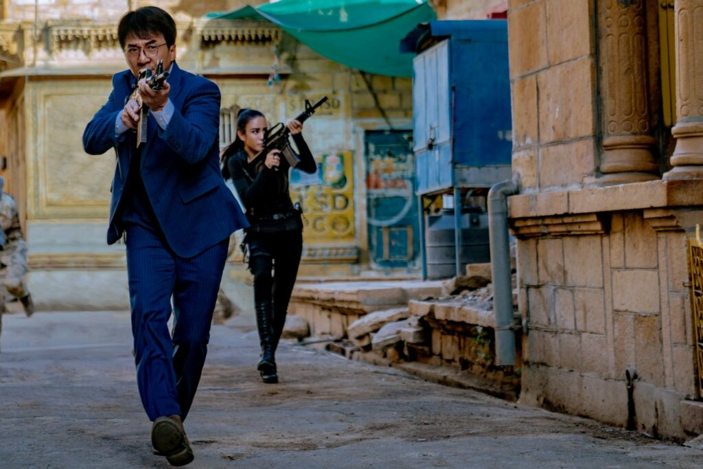 Jackie Chan, die Pistole im Anschlag, schreitet mit Brille und im blauen Anzug durch eine Gasse, während eine Kollegin in schwarzem Lederkostüm mit einem Maschinengewehr die Fenster im Auge behält - Neu auf Sky im August 2021