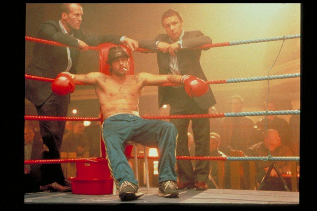 Mickey sitzt im Finale von Snatch gelassen im Boxring und raucht, Turkish und Tommy stehen hinter ihm und sehen besorgt aus.