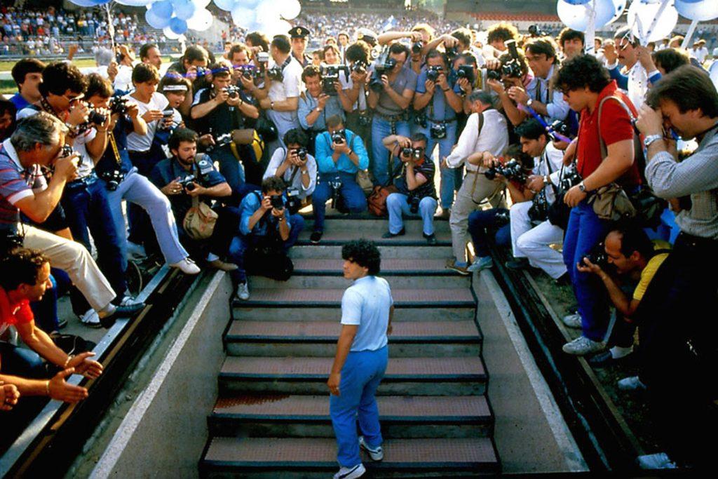 Diego Maradona auf einer Treppe, umringt von Reportern und Kameras