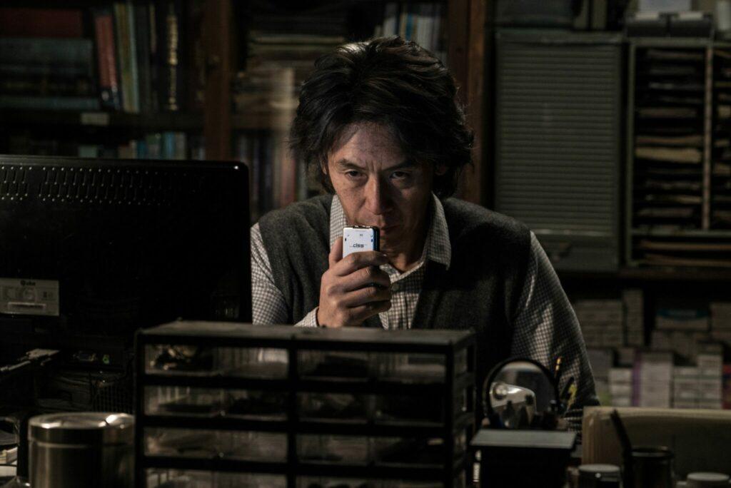 Byung-Su sitzt in Memoir of a Murderer in einem dunklen Raum und redet mit ernster Miene in ein Aufnahmegerät