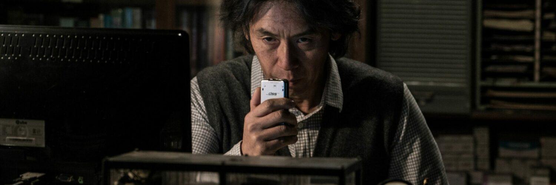 Byung-Su sitzt in einem dunklen Raum und redet mit ernster Miene in ein Aufnahmegerät