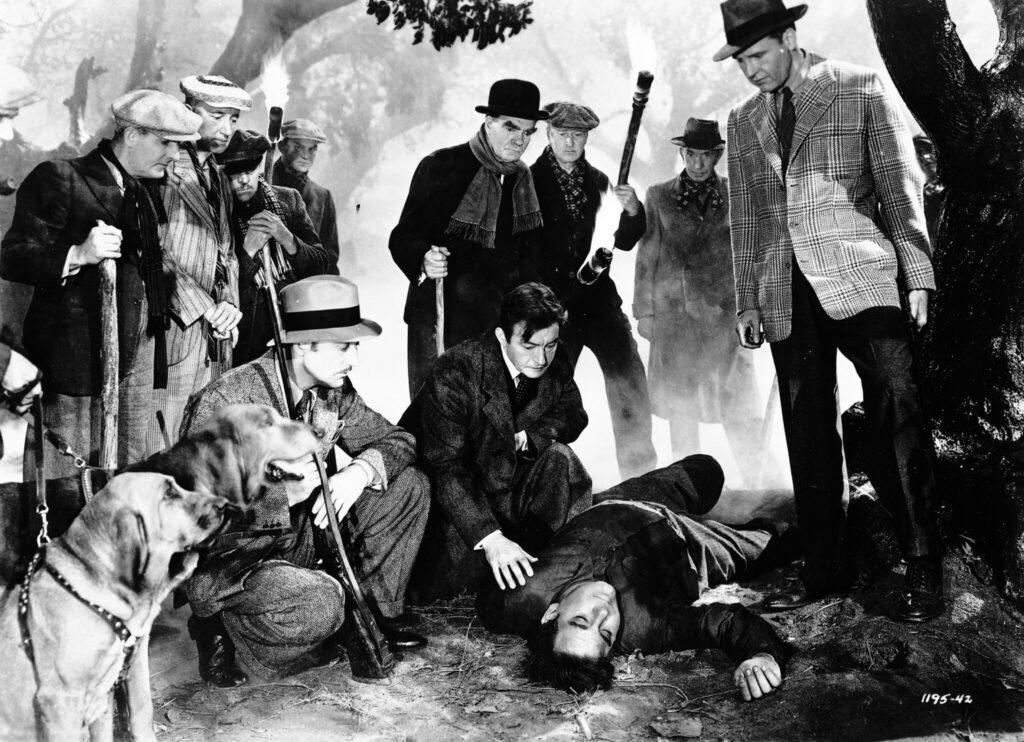 Die Jagdgesellschaft aus Bauern und Bürgern steht um einen vor ihnen liegenden, toten Mann herum - Universal Horror Filme