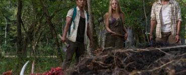 Jen, Darius und Luis stehen mit gezückten Waffen vor einer Leiche mit zerschmettertem Schädel
