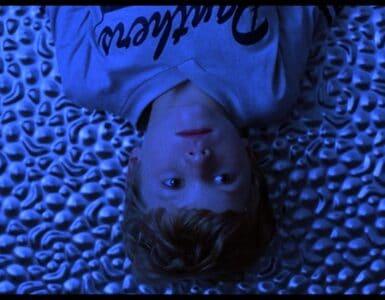 Getüncht ins lila Licht liegt der kleine Brian auf dem Boden in Mysterious Skin