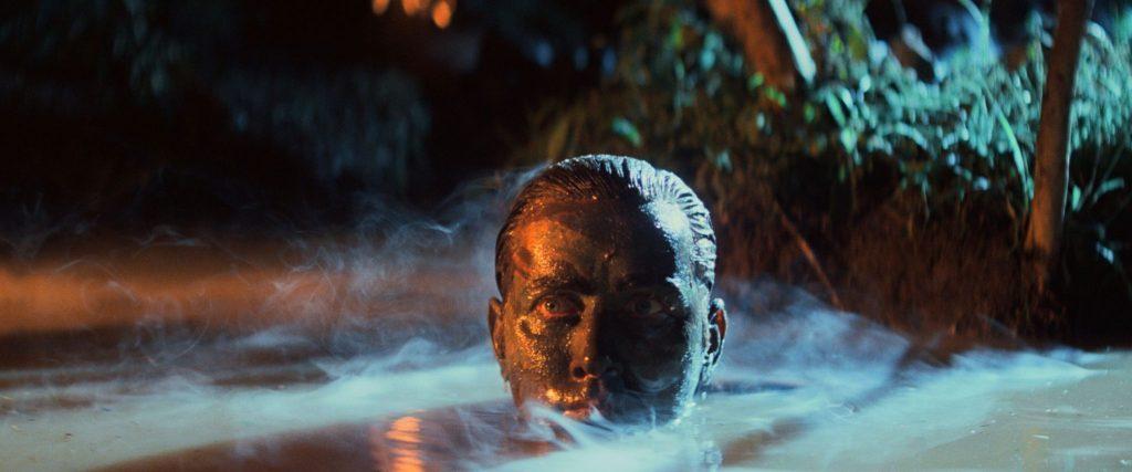 Captain Willard versteckt sich getarnt im nebeligen Sumpf, nur noch sein bemalter Kopf ist zu sehen