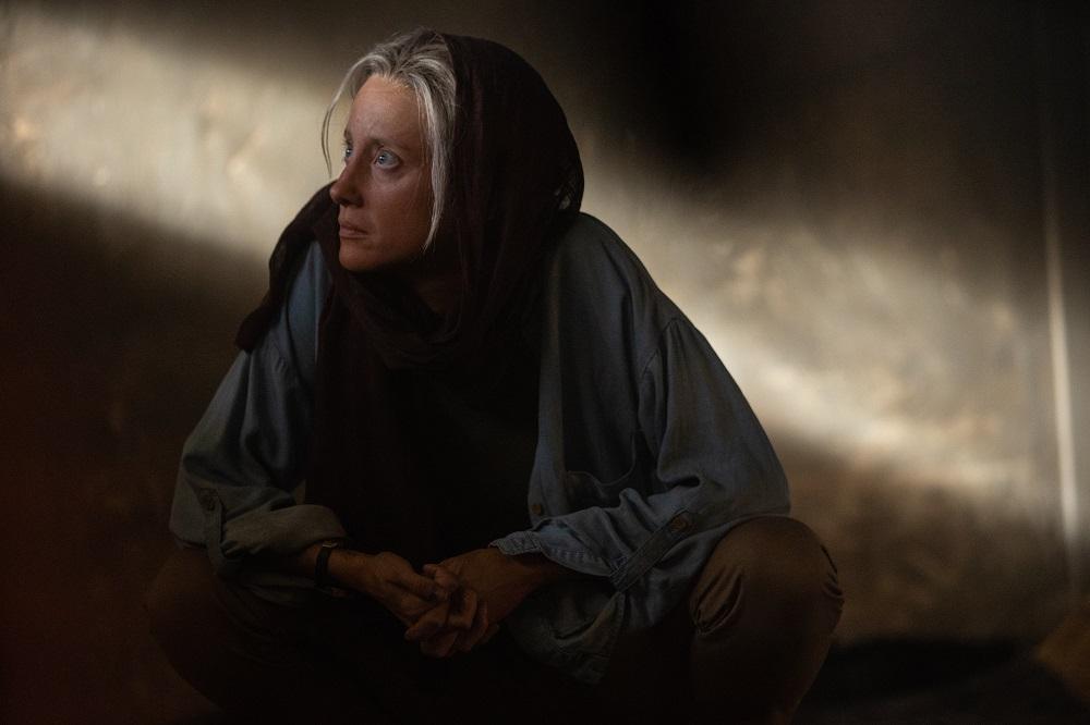 Emma Lynwood (Andrea Riseborough) hockt in einem dunklen, kahlen Raum und schaut nach links, von wo durch ein Fenster die Sonne hereinstrahlt in ZeroZeroZero © Studiocanal