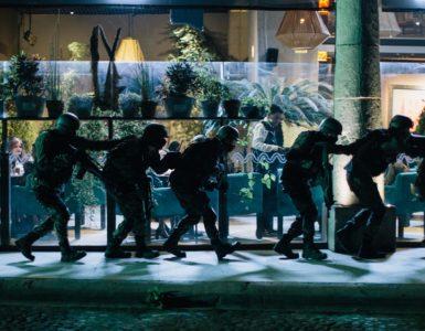 Eine Reihe gut ausgerüsteter Soldaten einer Spezialeinheit laufen voreinander her, im Hintergrund sieht man durch eine Glasscheibe Menschen in einer Art Restaurant sitzen in ZeroZeroZero © Studiocanal